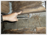 A-1 Home Inspection, Wood destroying insect damage. Finger penetrates floor joist to first knuckle.